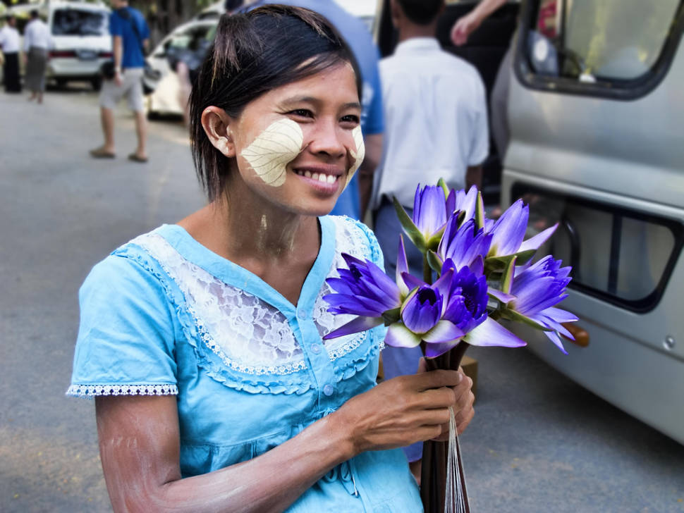 A pregnant woman sells water-lily blooms for offerings outside Kuthodaw Pagoda