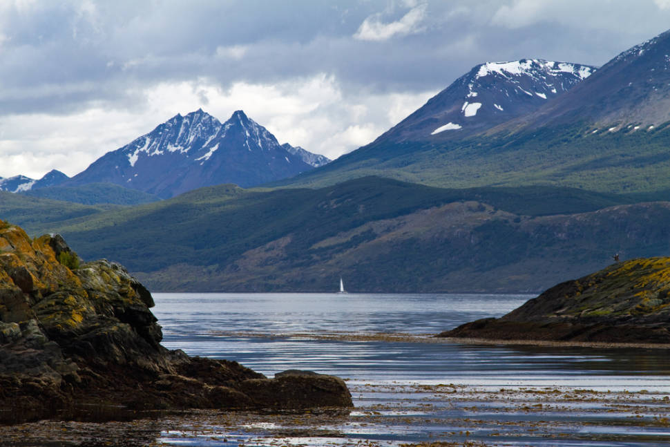 A lone sailboat in the distance is a very small thing against the backdrop of the Andes. Beagle Channel near Ushuaia, Argentina