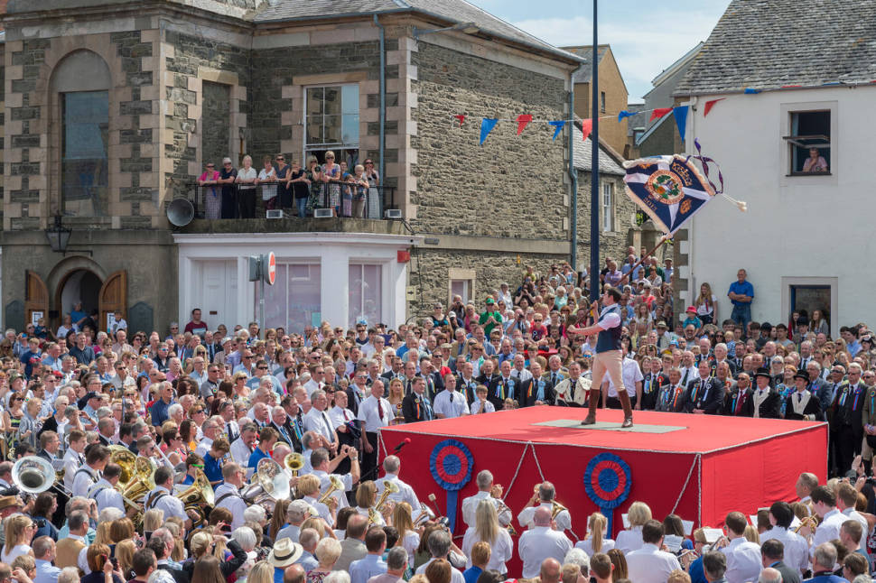 Selkirk Common Riding. Standard Bearer Scott Rodgerson casts the Burgh flag at the Casting Of The Colours ceremony