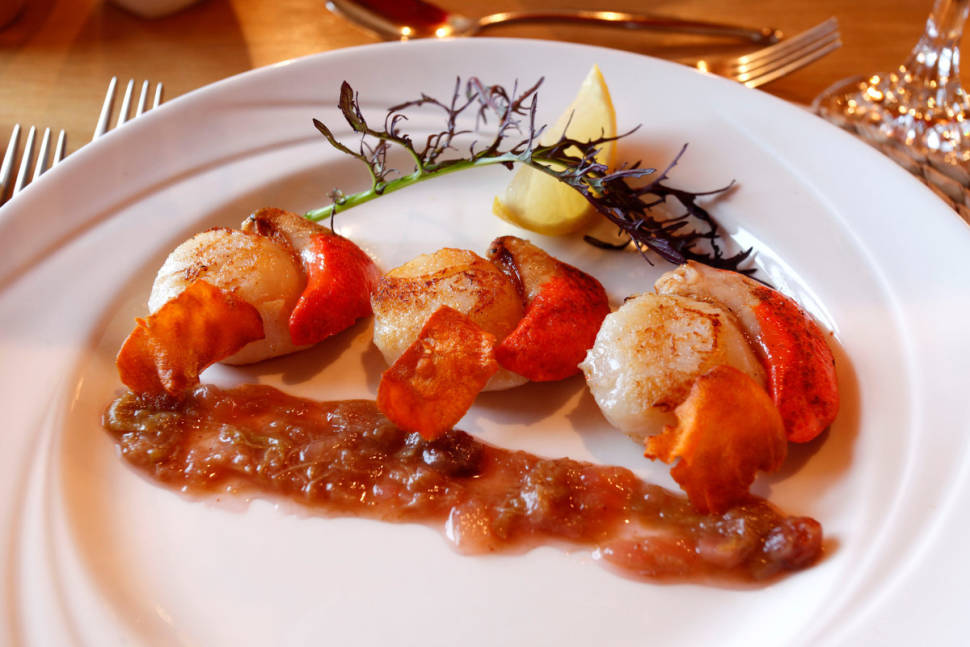 A starter of pan-seared Orkney scallops, served with pickled rhubarb and sweet potato crisps