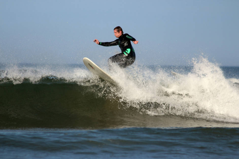 Surfer having fun on the waves at Pease Bay East Lothian Scotland
