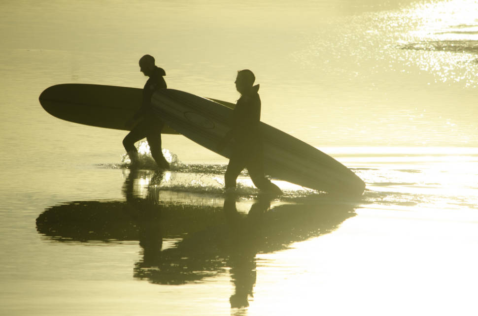 Surfers returning from a hard day's sport at Belhaven Bay, East Lothian