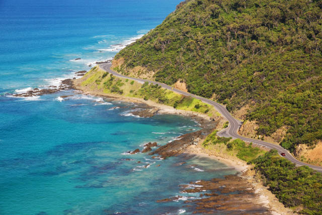 A little red car (spot it?) navigates the bends of the Great Ocean Road just past the town of Lorne