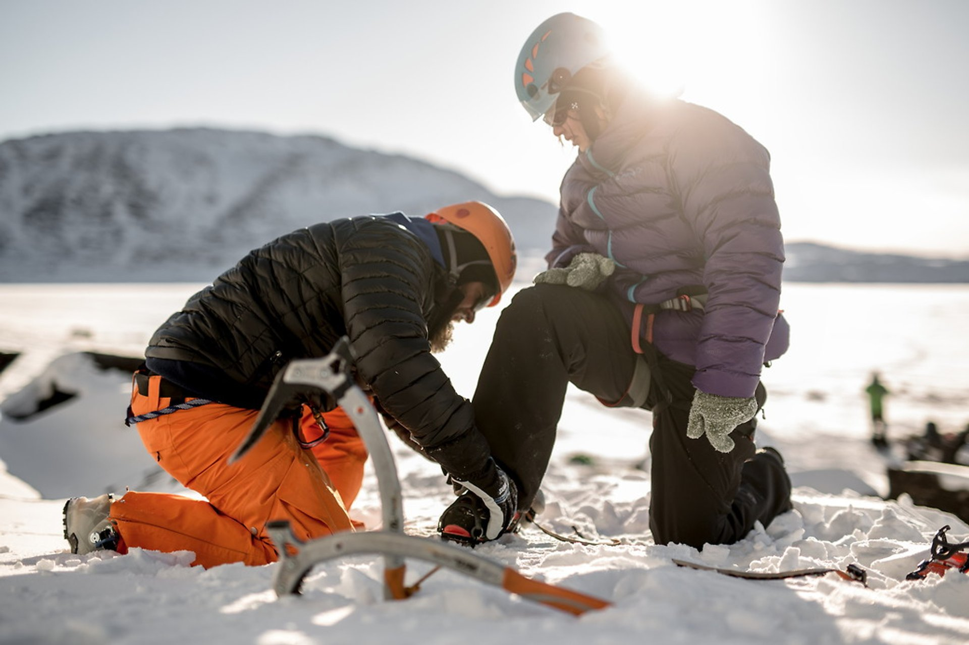 A guide helping a guest getting ready to go ice climbing in Greenland