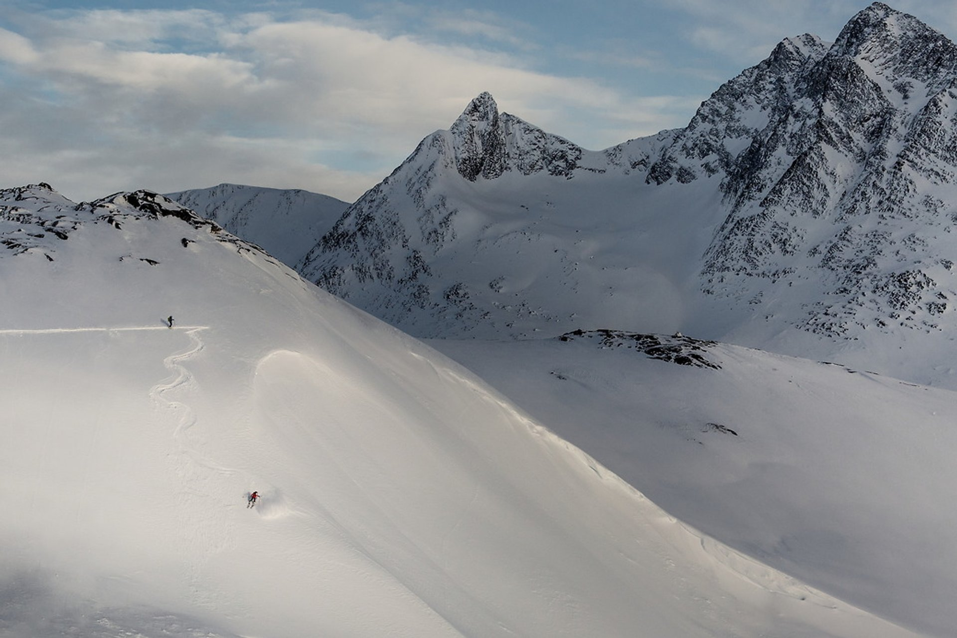 A skier carving a steep line near Kuummiut in East Greenland 2020