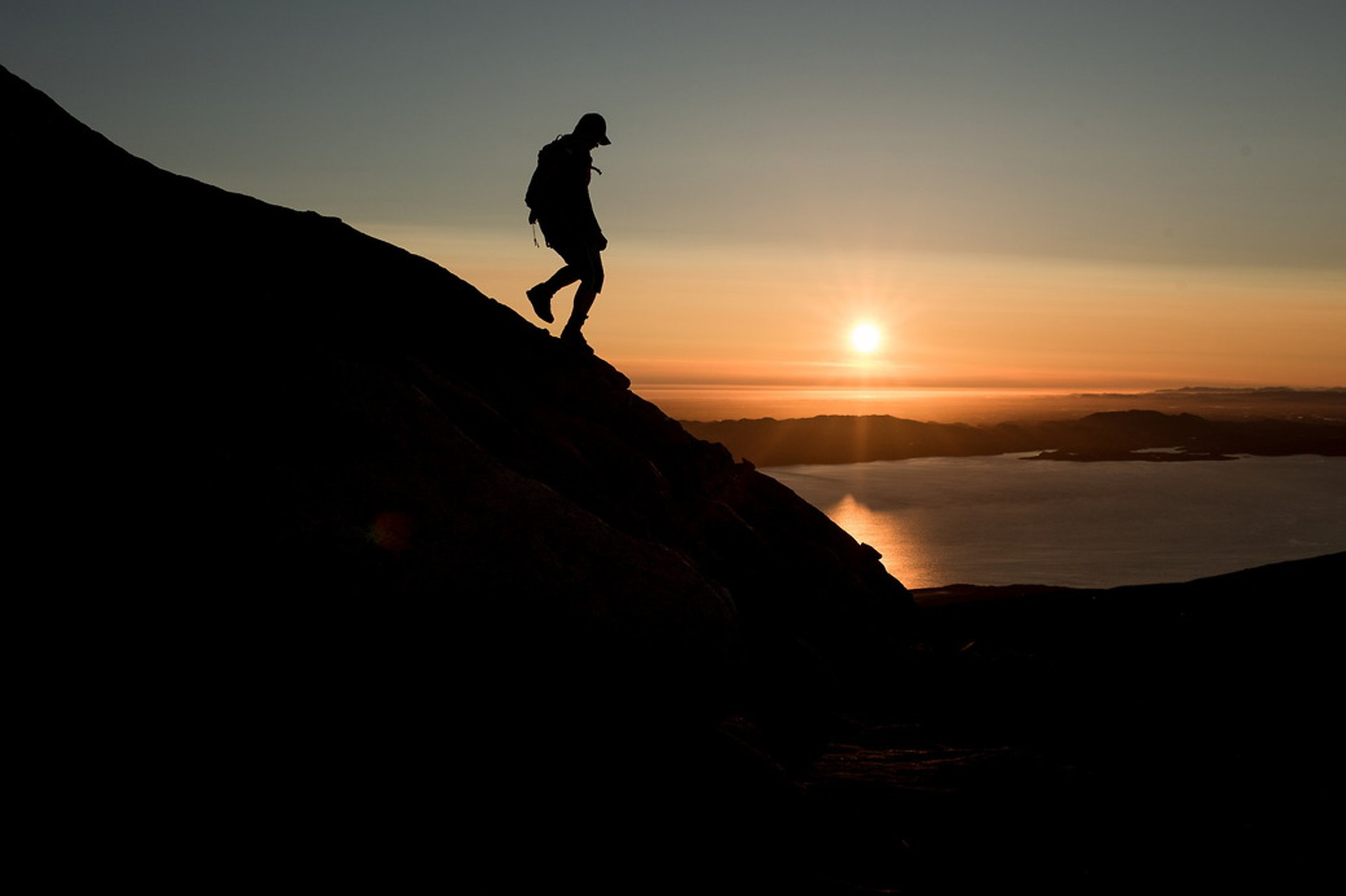 A hiker descending the mountain Ukkusissaq - Store Malene in the midnight sun outside Nuuk in Greenland 2020
