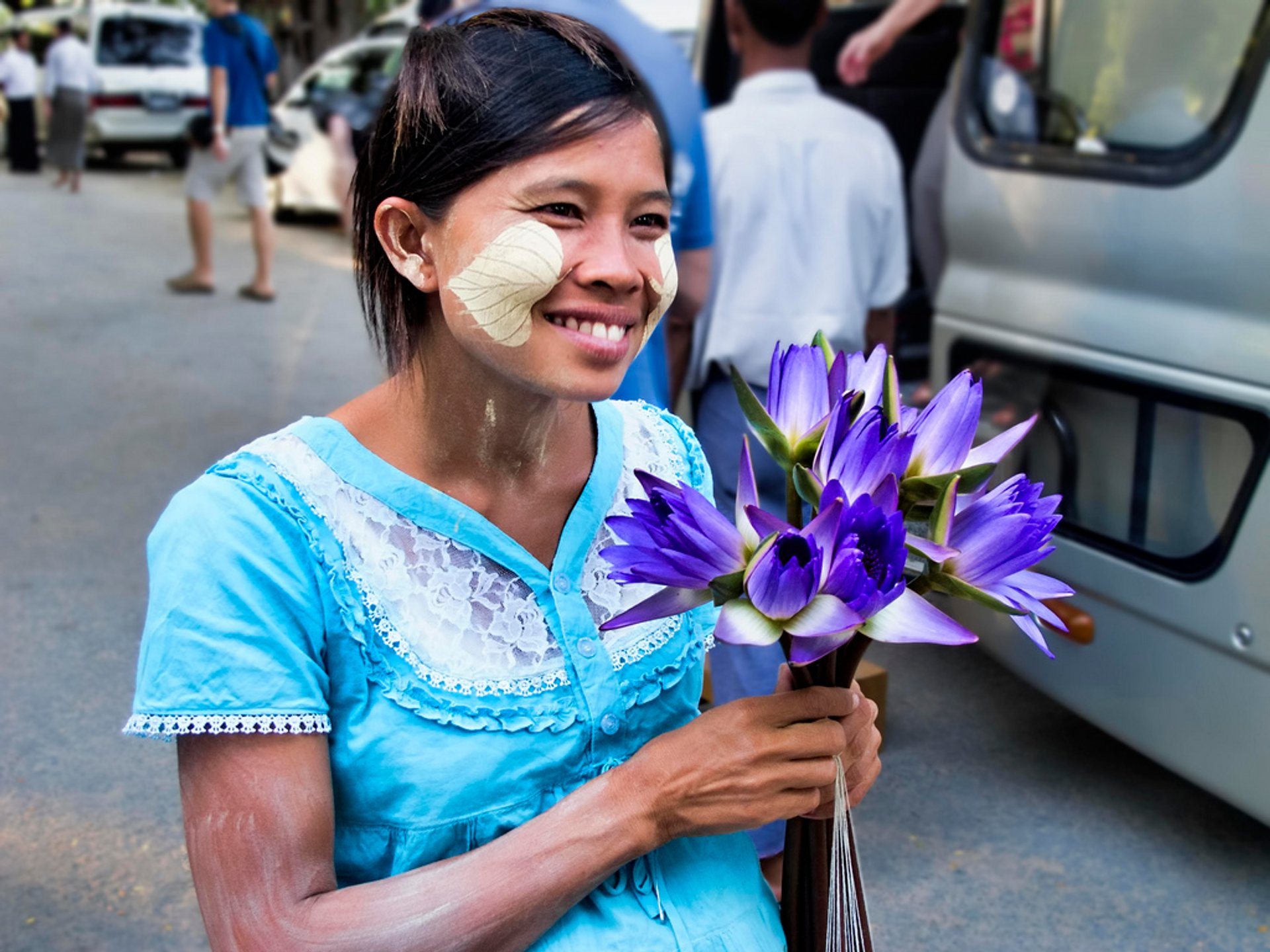 A pregnant woman sells water-lily blooms for offerings outside Kuthodaw Pagoda, Mandalay, Myanmar 2020