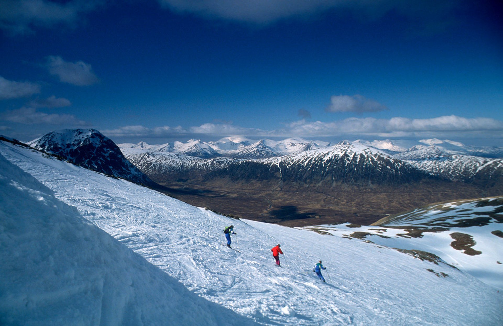 Skiers on their descent of one of the ski runs at the Glencoe Ski Centre with the mountains of Ben Nevis, Grey Corries and the Mamores beyond, Highland 2019
