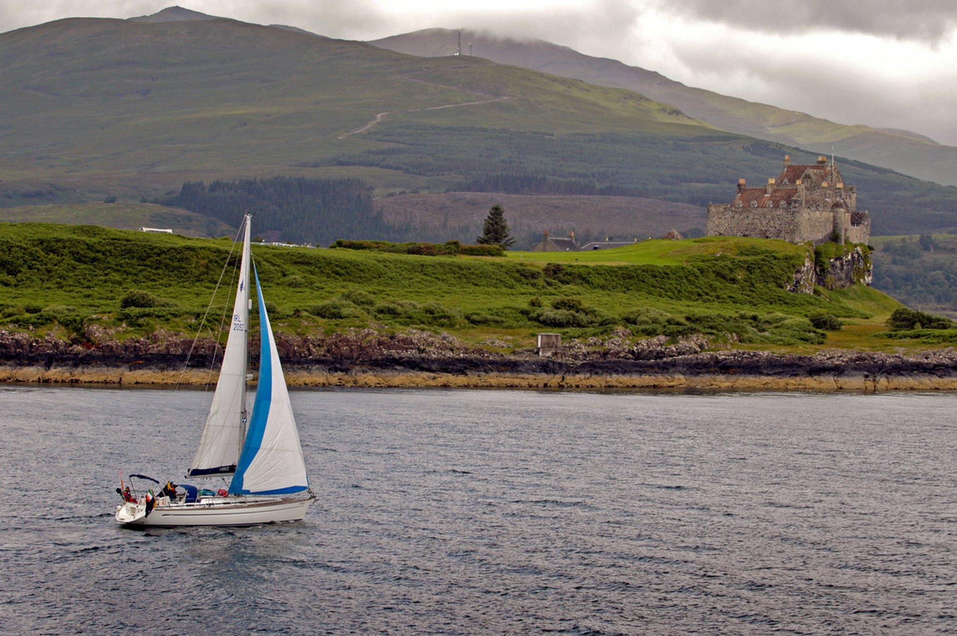 A yacht sailing in the Sound of Mull by Duart Castle on the Isle of Mull, Inner Hebrides 2020