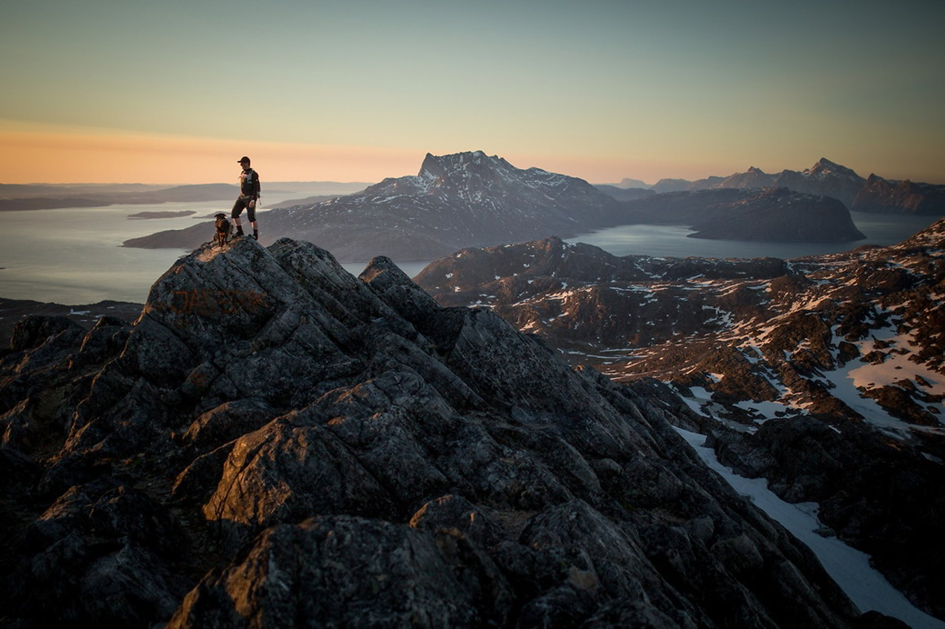 A hiker on Ukkusissaq - Stroe Malene in the midnight sun overlooking Sermitsiaq near Nuuk