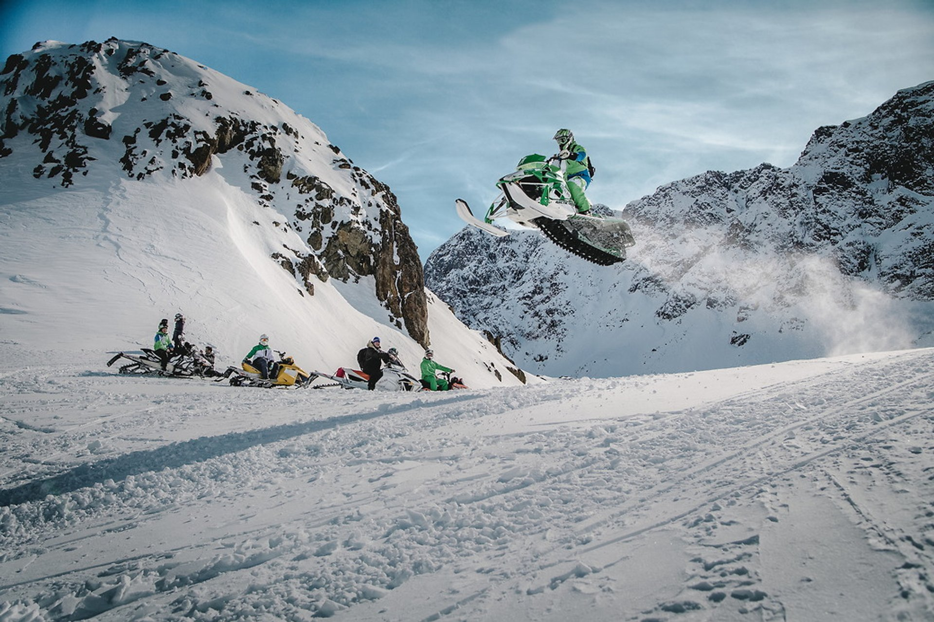 A snowmobiler flying high over a group of friends in the Sisimiut backckountry in Greenland 2019