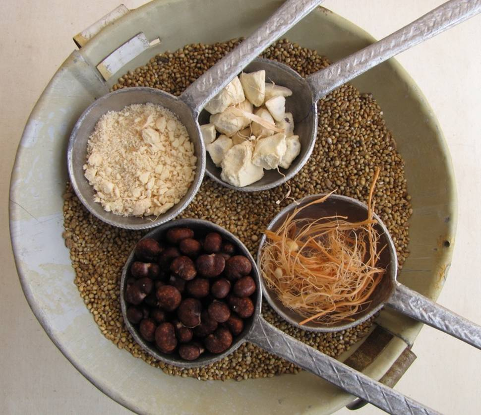 The dry, mature baobab fruit pulp chunks are shown compared to the three elements that comprise it: a white, opaque powdery edible pulp separated from pinkish fibers and brown baobab seeds.